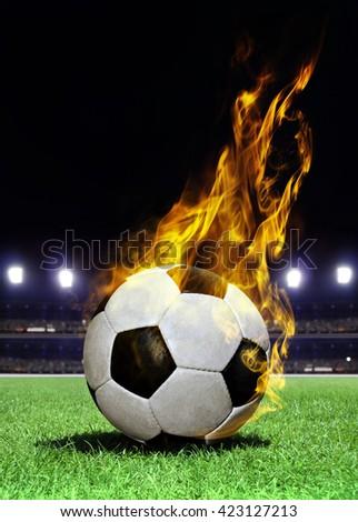 fiery soccer ball on playing field of stadium - stock photo