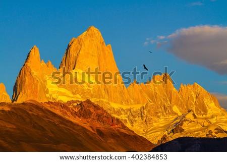 Fiery sunset illuminates the spectacular cliffs Fitz Roy. The stunning Patagonia - stock photo