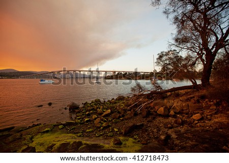 Fiery sunset on the River Derwent in Hobart, Tasmania, with Mount Wellington in background - stock photo