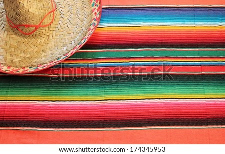 fiesta mexican poncho rug in bright colors with sombrero background with copy space - stock photo