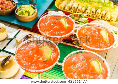 Fiesta party buffet table with watermelon margaritas and other traditional Mexican food. - stock photo