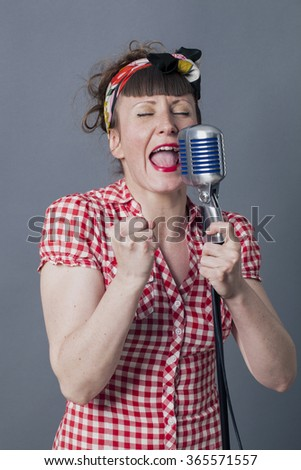fifties singer in studio - passionate young woman with retro style singing in old fashioned mike, gray background - stock photo