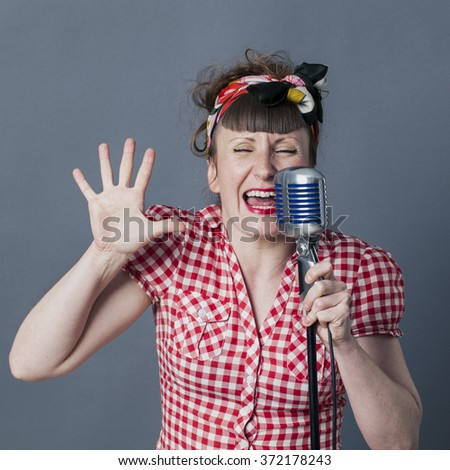 fifties singer in studio - performing young female rocker and vocal artist with retro style singing in old fashioned microphone, gray background - stock photo
