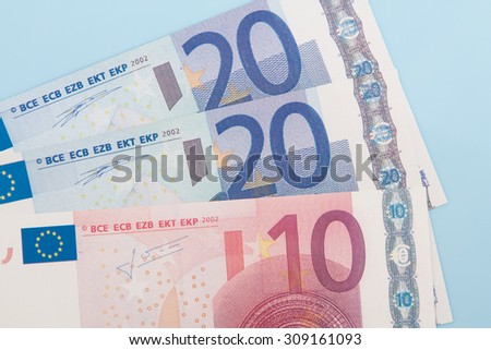 Fifty euro in various notes on light blue background - stock photo