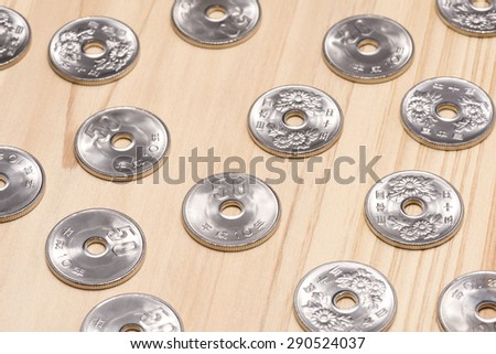 fifty yen on wooden table - stock photo
