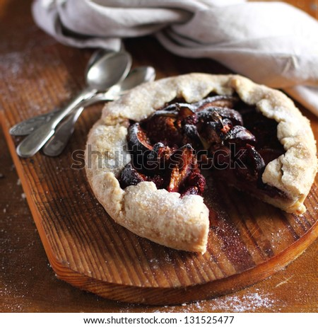 Fig and raspberry galette pie with icing sugar on a wooden cutting board - stock photo