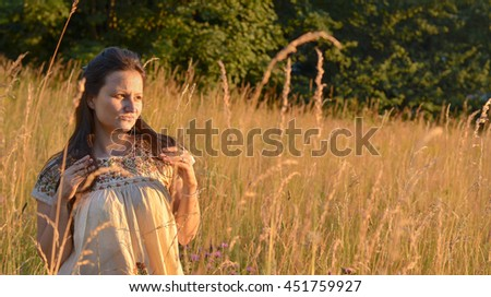 Fight depression - young woman trying to relax in nature. Woman standing alone in meadow at sunset. Stress relief concept. - stock photo
