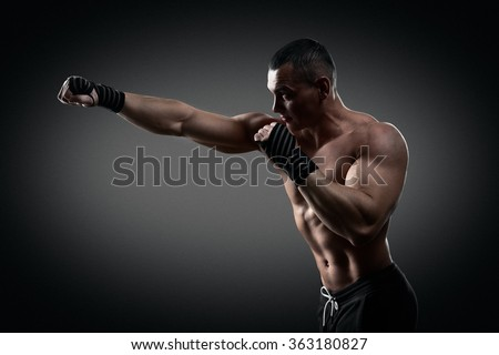 Fighter boxer standing staring strong on black background. Young masculine caucasian male athlete. - stock photo