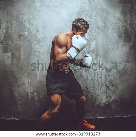 Fighter in white boxing gloves over grey wall. - stock photo