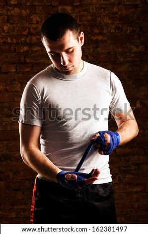 fighter is getting ready against brick wall - stock photo