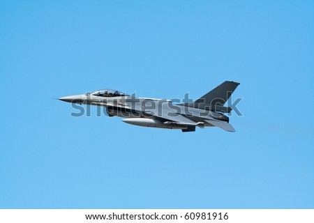 fighter jet flying with a blue sky background - stock photo