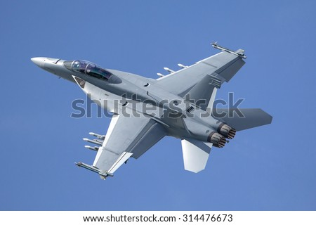 Fighter jet loaded with missiles flying against a blue sky - stock photo