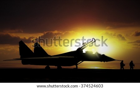 Fighter jet under sunset on super carrier at sea - stock photo