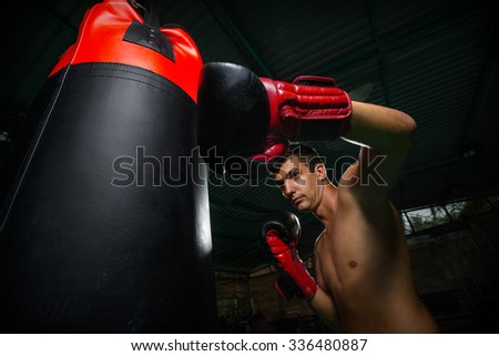 Fighter Practicing Some Kicks With Punching Bag - A Man With A Tattoo Boxing On dark Background - stock photo