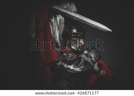 Fighter, Praetorian Roman legionary and red cloak, armor and sword in war attitude - stock photo