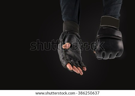 fighter's hand in gloves for martial arts, on the black background. space for text, logo. - stock photo