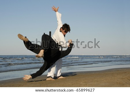 fighting of two men in taekwondo and apkido sports on the beach - stock photo