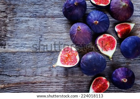 figs on a dark wood background. tinting. selective focus on the middle figs slice - stock photo
