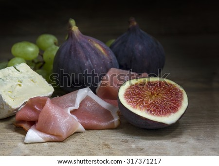 Figs with ham and cheese on a rustic wooden table, food still life with selected focus, narrow depth of field, dark background - stock photo