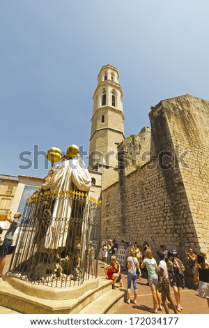 FIGUERES, SPAIN - JUNE 14: Tourists at Dali Museum Square and facing the cathedral in Figueres, on June 14, 2012. Museum was opened on 1974 and houses largest collection of works by Salvador Dali. - stock photo