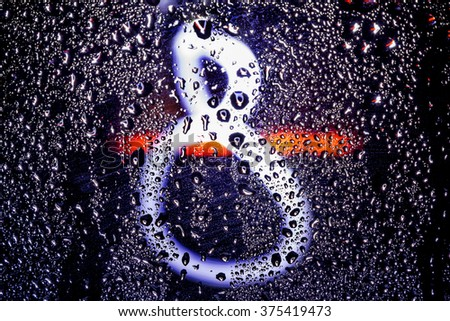 Figure eight glows through the wet glass amid colorful Bokeh - stock photo