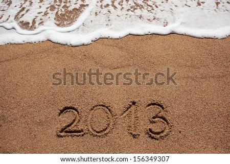 Figure in 2013 was written on the sea shore - stock photo