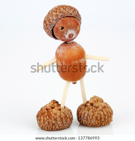 Figure made of acorns and matches - stock photo