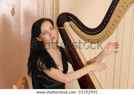 Figure of the young beautiful woman against a harp - stock photo