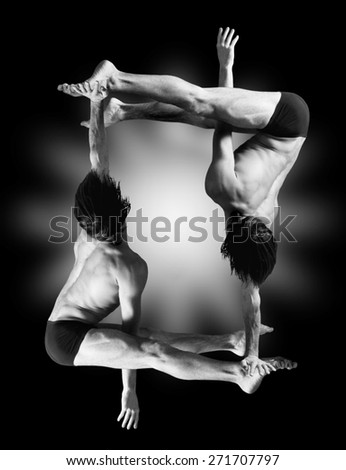 Figures gymnasts on a black background.Athletes.Handstand.Black and white image - stock photo