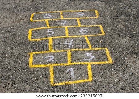 Figures in childish game hopscotch painted with yellow paint on asphalt - stock photo