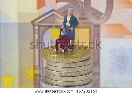 Figurine from senior and euro coins and banknote background - stock photo