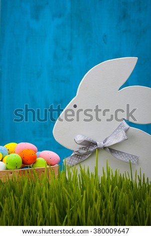 Figurine of a rabbit and a basket of Easter eggs in the grass on a blue background. - stock photo