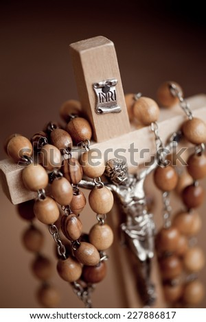 Figurine of Jesus in wood rosary made of beads dangle on wooden cross, INRI sign above, vertical orientation, nobody. - stock photo