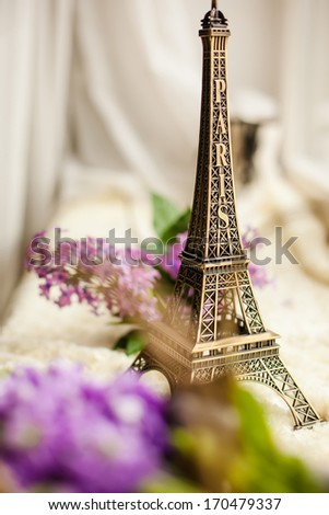 figurine of The Eiffel Tower and lilac flowers, close-up - stock photo