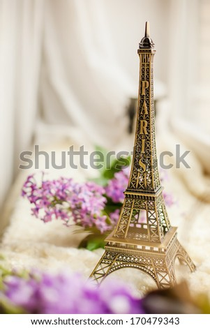 figurine of The Eiffel Tower and lilac flowers, close-up, with blurring foreground - stock photo