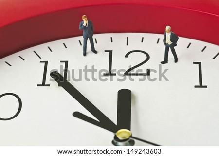 Figurine on clock face - concept - Five to twelve - stock photo
