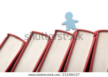 Figurine on the spine of books isolated on white background  - stock photo