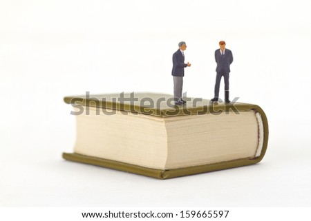 Figurine standing on a book - stock photo