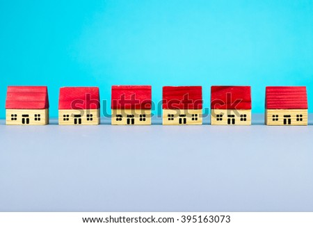 Figurine wooden houses on blue background - stock photo