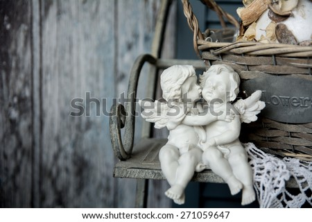 Figurines angels sitting on a bench. Romance on the background of old boards - stock photo