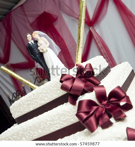 figurines of bride and groom on a wedding cake - stock photo