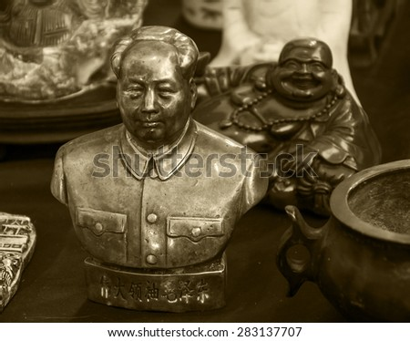 Figurines of Chinese former Chairman Mao and of laughing Buddha at background. Still life at flea market in Paris (France). Contrasts in life idea. Aged photo. Sepia. - stock photo