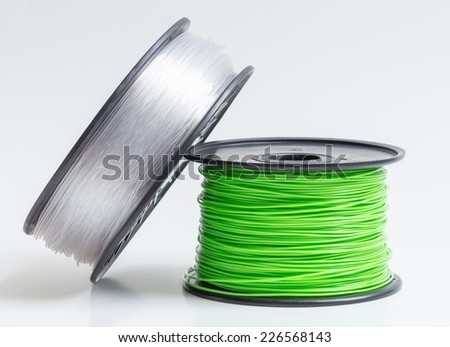 Filament for 3D Printer crystal clear and bright green against a bright background. - stock photo
