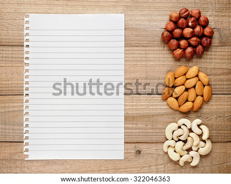 Filberts, almonds, cashew nuts and paper for recipe on wooden background - stock photo