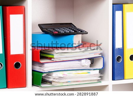 File folders and calculator on the shelves at office - stock photo