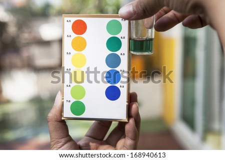 file of hand holding water ph testing test comparing color to indicated  - stock photo