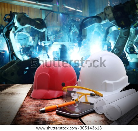 file of safety helmet and drawing  on wood table with group robot welding automotive industrail background  - stock photo