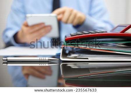 files and folders and businessman in background with tablet pc in hands - stock photo