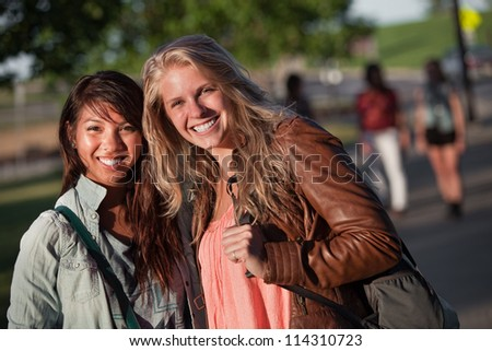 Filipino and European teenage girlfriends on campus - stock photo