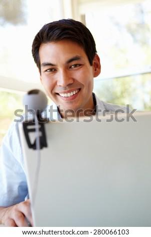 Filipino man using skype - stock photo